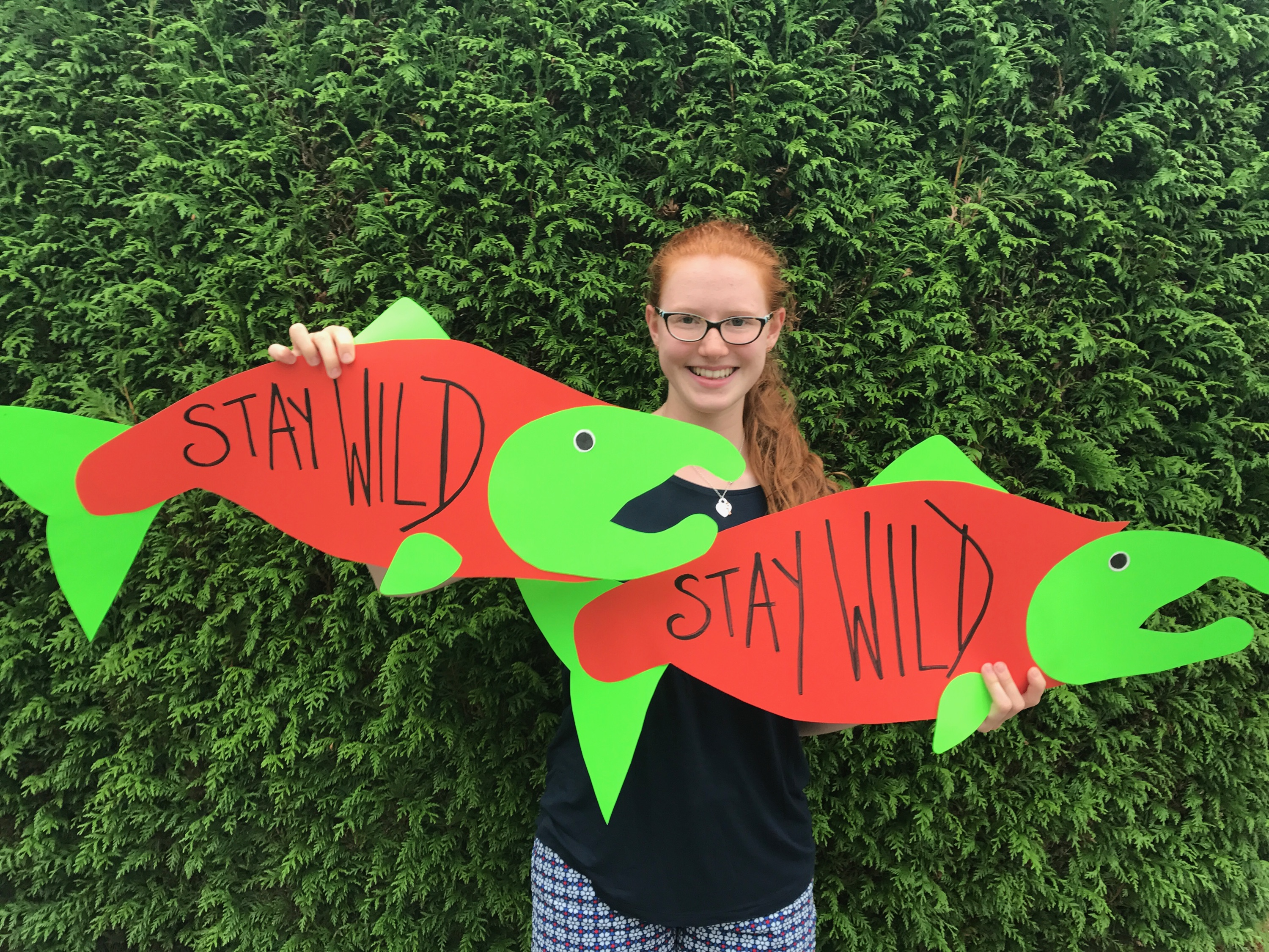 Amadea de Wit, Grade 11 student at Southridge, holds 'Stay Wild' signs