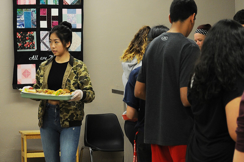 Southridge Grade 12 student Angela Cheng delivers a tray of food to guests at SUMS on Friday. (Aaron Hinks photo)